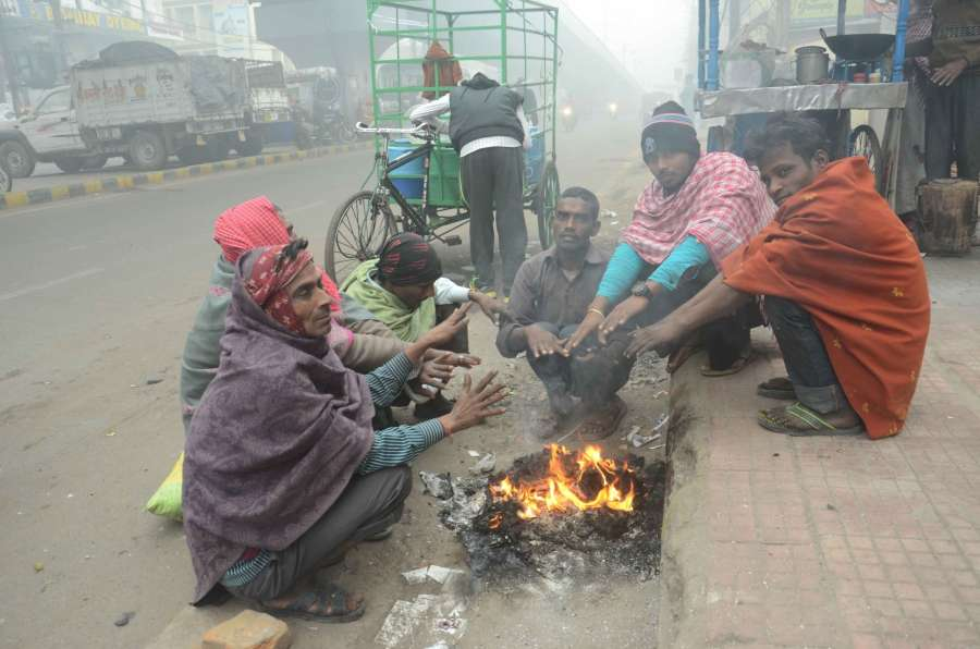 Patna: People warm themselves around a bonfire during a cold winter day in Patna on Dec 6, 2016. (Photo: IANS)