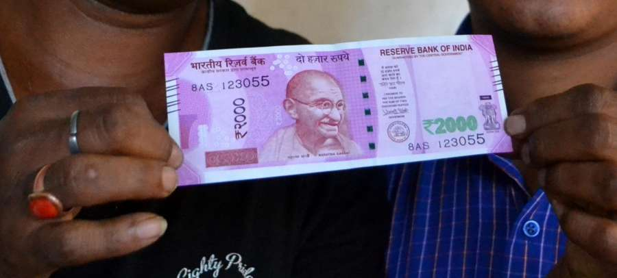 Guwahati: A man shows the new Rs 2000 currency note in Guwahati on Nov. 10, 2016. (Photo: IANS)