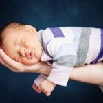 Portrait of newborn baby girl lying on father's arm by .