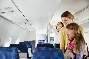 Woman and daughter finding their seats in airplane by .