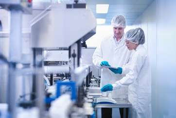 Workers inspecting product in pharmaceutical factory by .