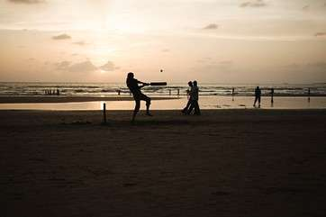 People playing cricket on mumbai beach by .
