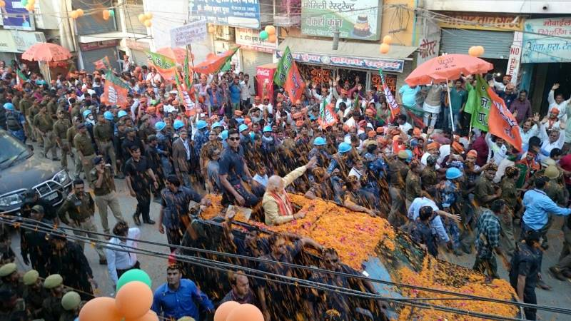 Varanasi:People shower flower petals on Prime Minister Narendra Modi during a roadshow in Varanasi on March 5, 2017. (Photo: IANS) by .