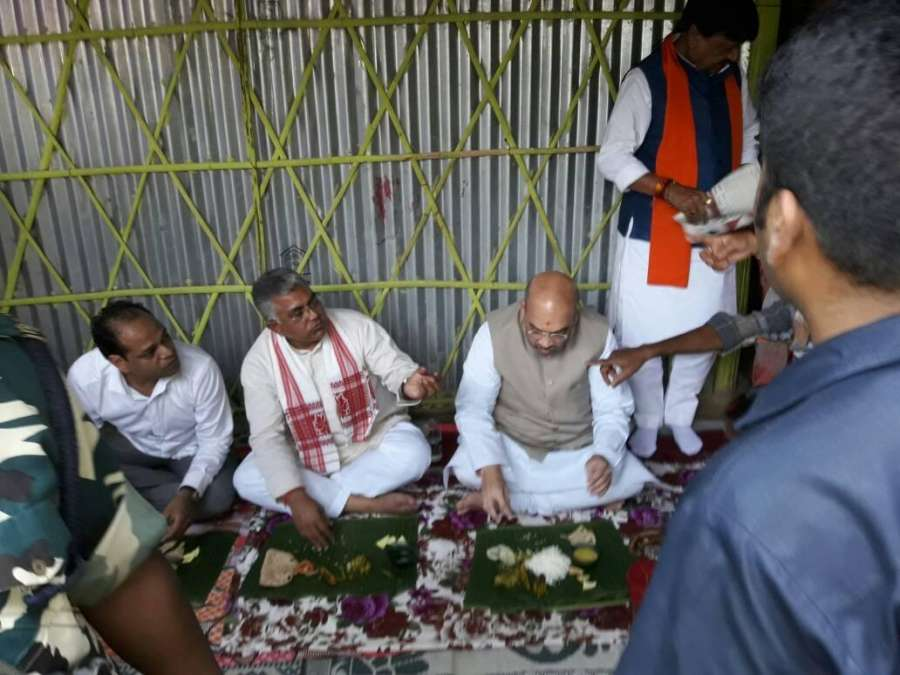 Naxalbari: BJP chief Amit Shah and West Bengal party chief Dilip Ghosh have food sitting on ground during their visit to Kotiyajote in Naxalbari near Siliguri on April 25, 2017. (Photo: IANS) by .