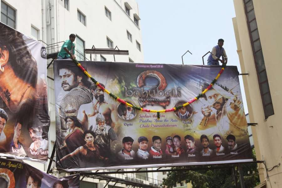 """Mumbai: Fans wash a poster of """"Baahubali 2"""" with milk after the film was released in Chennai, on April 28, 2017. (Photo: IANS) by ."""