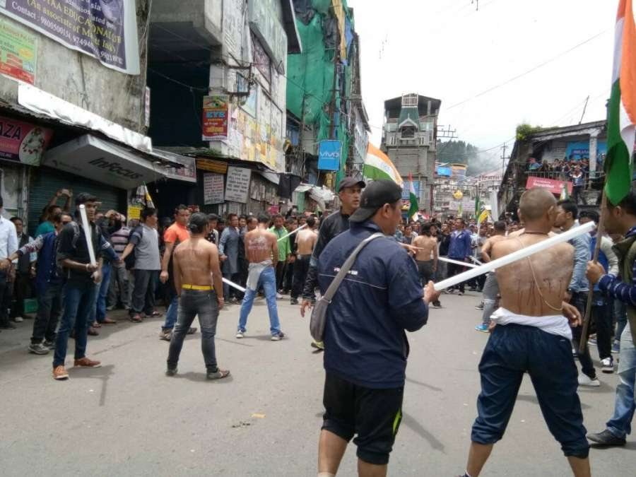 """Darjeeling: Activists of the Yuva Morcha - the youth wing of the GJM a """"tubelight rally"""" and broke the tubelight rods on their back to protest against state government and police action in Darjeeling on June 27, 2017. (Photo: IANS) by ."""