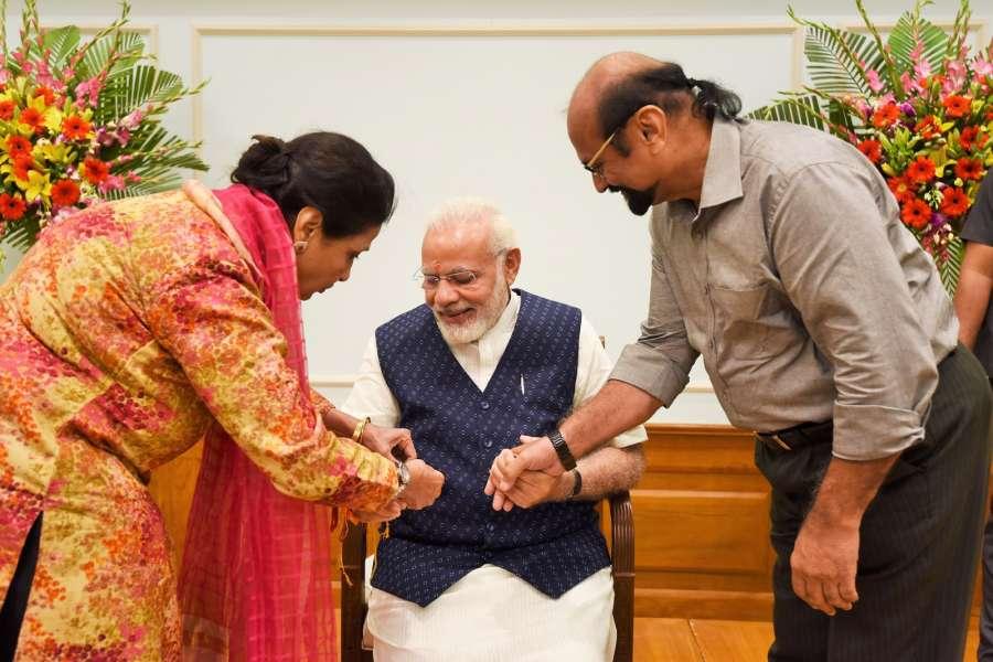 New Delhi: A woman ties 'Rakhi' on Prime Minister Narendra Modi's wrist, on Raksha Bandhan, in New Delhi on Aug 7, 2017. (Photo: IANS/PIB) by .