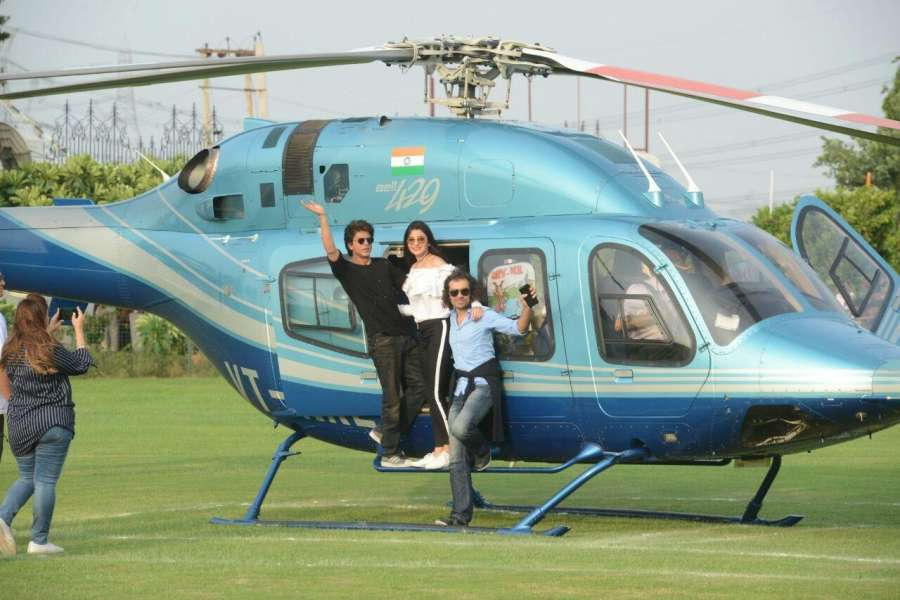 """Gurugram: Actors Anushka Sharma and Shah Rukh Khan along with Filmmaker Imtiaz Ali deboard a helicopter at a Gurugram University where they arrived to promote their upcoming film """"Jab Harry Met Sejal"""" on Aug 3, 2017. (Photo: IANS) by ."""