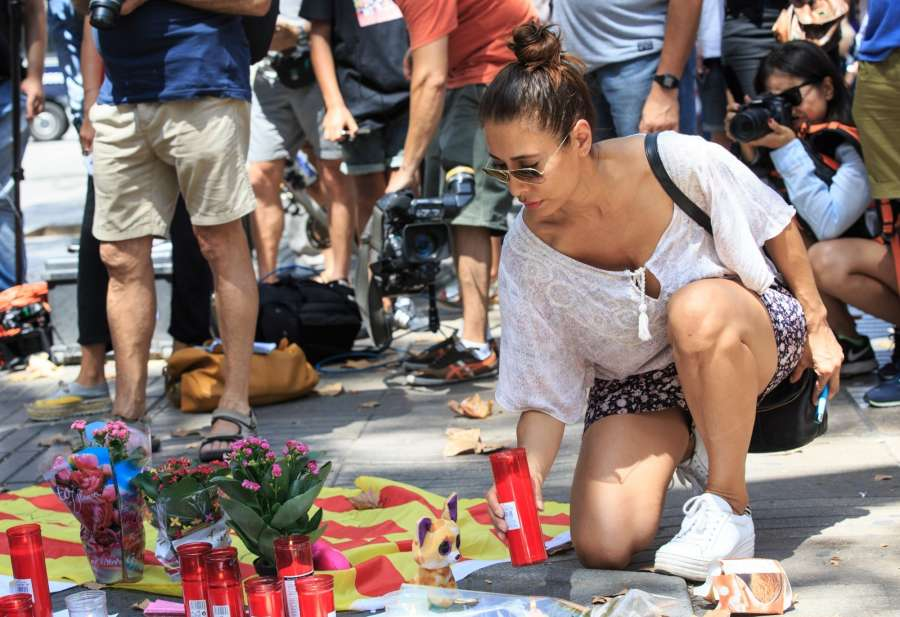 BARCELONA, Aug. 18, 2017 (Xinhua) -- A woman mourns victims of the terror attack on Las Ramblas area, Barcelona, Spain, on Aug. 18, 2017. At least 14 died in Thursday's double terror attacks in Spain, as Spanish people demonstrated defiance and condolences by leaders of the world poured in on Friday. (Xinhua/Xu Jinquan/IANS) by .