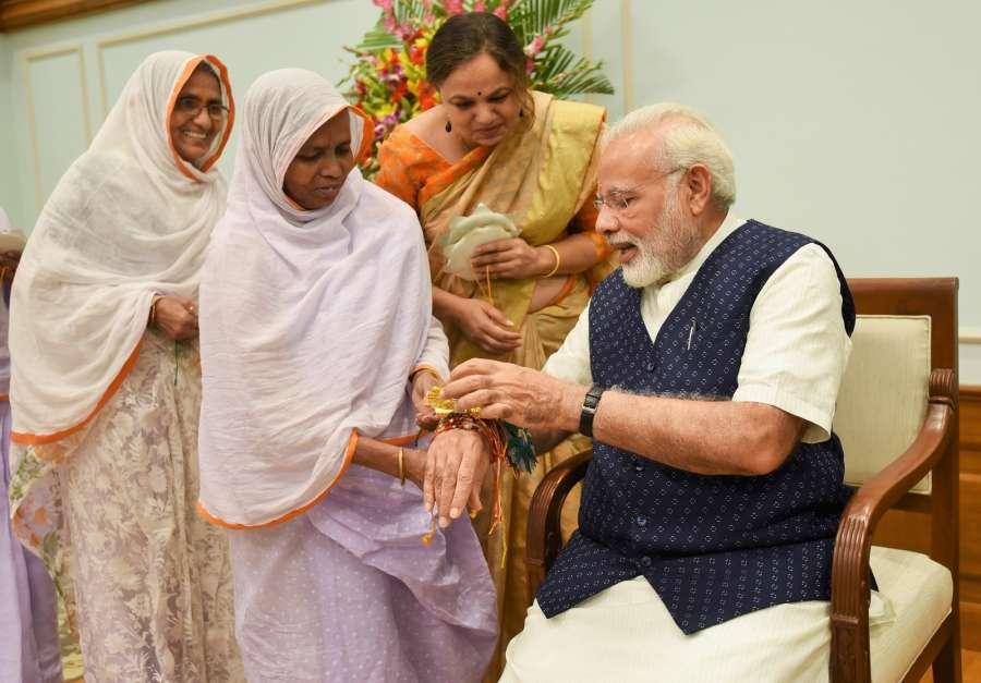 New Delhi: Widows tie 'Rakhi' on Prime Minister Narendra Modi's wrist on 'Raksha Bandhan' in New Delhi on Aug 7, 2017. (Photo: IANS/PIB) by .