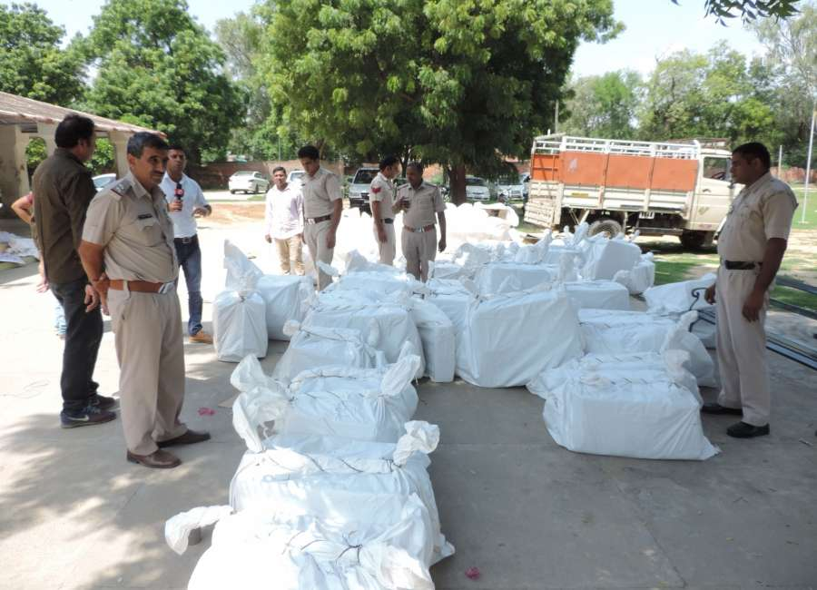 Sirsa: Police with the seized illegal belongings found inside the premises of the Dera Sacha Sauda headquarters on Day 2 of the search by security forces and authorities near Sirsa in Haryana on Sept 9, 207. (Photo: IANS) by .