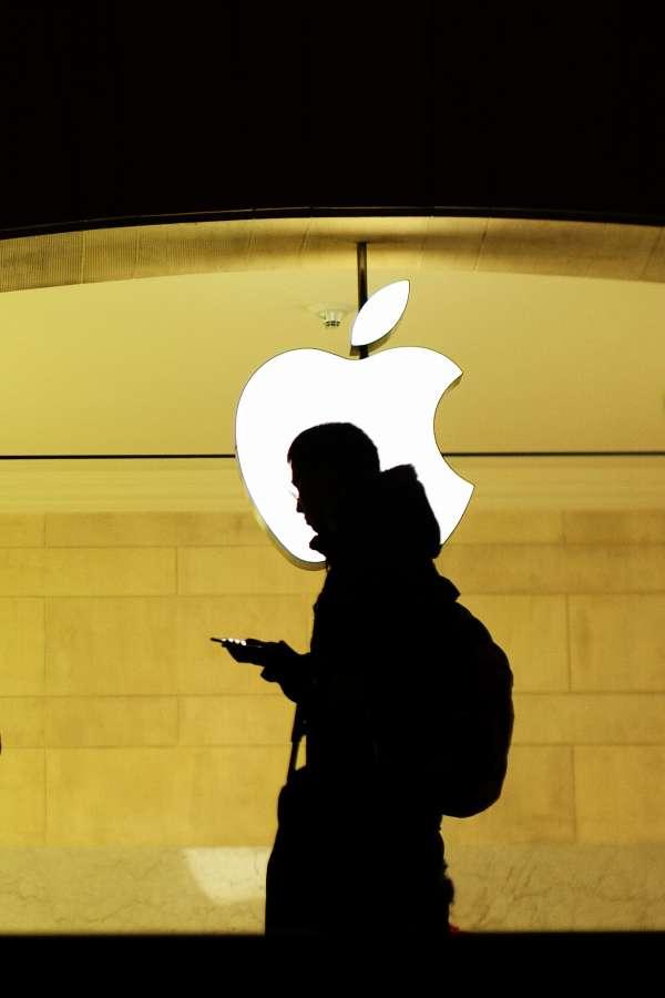 A man checks his phone at the Apple store.