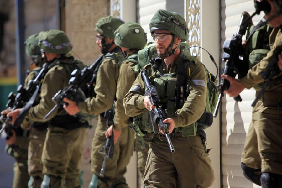 HEBRON, March 31, 2018 (Xinhua) -- Israeli soldiers take positions during a clash with Palestinian protesters in the West Bank city of Hebron, on March 31, 2018. The clash broke out after Friday that left some 15 Palestinians killed and more than 1,400 wounded by the Israeli Defense Forces gunfire in the clashes along the Israel-Gaza border. (Xinhua/Mamoun Wazwaz/IANS) by .