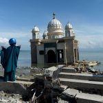 PALU, Oct. 8, 2018 (Xinhua) -- A woman stands near the debris of a damaged mosque on Talise beach in Palu, Central Sulawesi, Indonesia. Death toll from multiple powerful quakes and an ensuing tsunami striking Central Sulawesi province of Indonesia on September 28 jumped to 1,948 on Monday and more than 5,000 others went missing, according to a disaster agency official here. (Xinhua/Agung Kuncahya B/IANS) by .