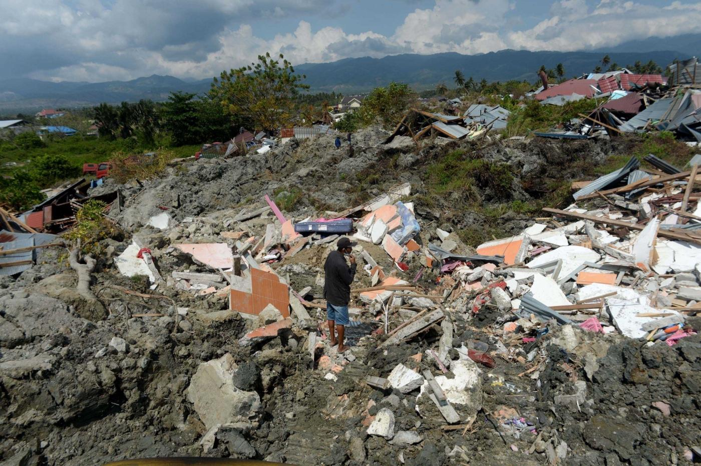 PALU, Oct. 3, 2018 (Xinhua) -- A local resident stands on the ruins at Petobo, in Palu, Central Sulawesi, Indonesia. Oct. 3, 2018. The death toll from Indonesia's multiple earthquakes and an ensuing tsunami jumped to 1,407 on Wednesday, the country's disaster management agency said. (Xinhua/Agung Kuncahya B./IANS) by .