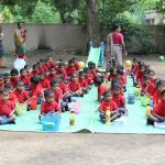 Students dressed in their red school uniforms assemble in the lawn for nutritious meals provided by the school. by .