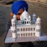 Amritsar: Paper artist Gurpreet Singh shows a model of Kartarpur Sahib, the final resting place of Guru Nank Dev, created by him, on the eve of the first Sikh Guru's birth anniversary, in Amritsar on Nov 22, 2018. (Photo: IANS) by .