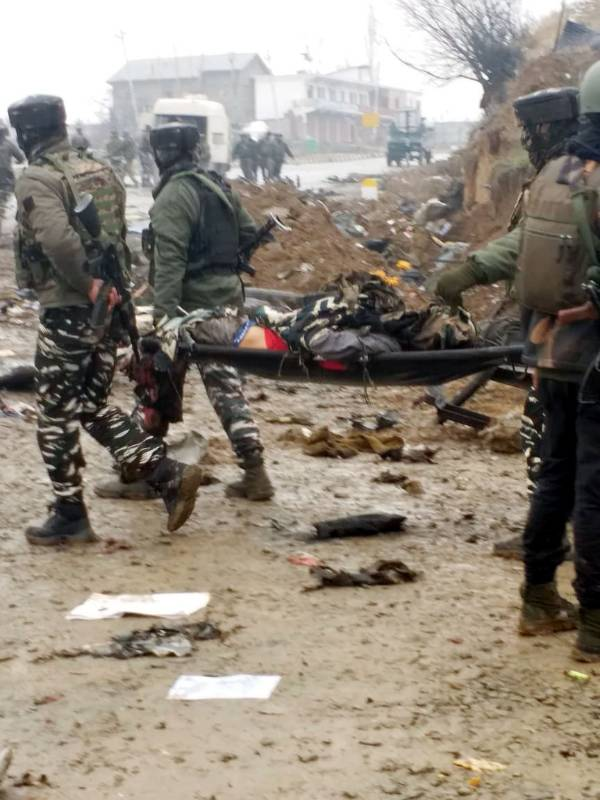 Pulwama: Security personnel takes away a victim of suicide bomb blast in Jammu and Kashmir's Pulwama district, on Feb 14, 2019. Ten Central Reserve Police Force (CRPF) troopers were killed and 15 others injured in an audacious suicide attack by militants on the Srinagar-Jammu highway. The militants detonated an improvised explosive device (IED) targeting a CRPF bus in Lethpora area, about 30 km from here, around 3.15 p.m.(Photo: IANS) by .