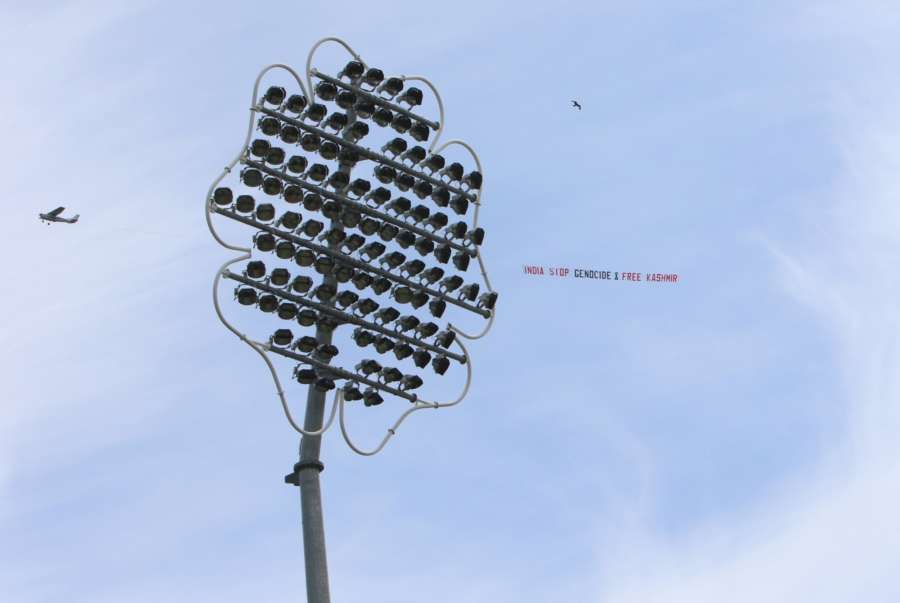 """Leeds: A low flying airplane tows a large aerial banner reading """"India Stop Genocide & Free Kashmir"""" in the skies above the Headingley Stadium where the 44th match of World Cup 2019 between India and Sri Lanka is underway in Leeds, England on July 6, 2019. (Photo: Surjeet Yadav/IANS) by ."""