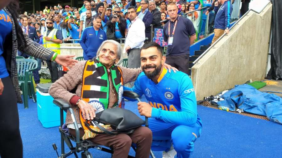 """Birmingham: India skipper Virat Kohli greets 87-year-old Charulata Patel, who became a social media sensation after an image of her blowing a horn to cheer the Men in Blue during their World Cup match against Bangladesh went viral, at the Edgbaston Cricket Ground on July 2, 2019. """"I have been watching cricket for last many decades. Earlier, I used to watch on TV when I was working, but now that I am retired I watch it live,"""" she said. (Photo: IANS) by ."""