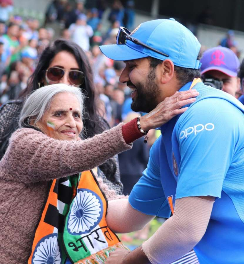 """Birmingham: India opener Rohit Sharma greets 87-year-old Charulata Patel, who became a social media sensation after an image of her blowing a horn to cheer the Men in Blue during their World Cup match against Bangladesh went viral, at the Edgbaston Cricket Ground on July 2, 2019. """"I have been watching cricket for last many decades. Earlier, I used to watch on TV when I was working, but now that I am retired I watch it live,"""" she said. (Photo: IANS) by ."""