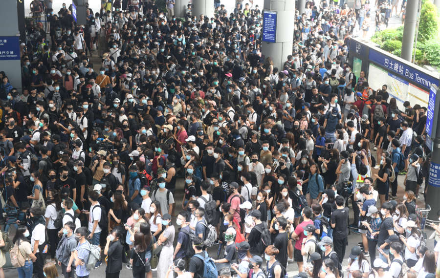 HONG KONG, Sept. 1, 2019 (Xinhua) -- Radical protesters block the exit to bus terminal at Hong Kong International Airport in south China's Hong Kong, Sept. 1, 2019. A large group of radical protesters charged security cordon lines, damaged facilities, and disrupted the operations of the Hong Kong International Airport on Sunday. n Protesters started gathering at the bus stops of the airport terminal at 1:00 p.m. local time. Around 2:00 p.m., the radical protesters started to charge water-filled barriers, pointed laser beams at the airport authority staff, and blocked roads with trolleys and mills barriers. n They also hurled objects at police officers and airport authority staff. Some radical protesters used iron bars to smash the doors of airport facilities. n At around 3:30 p.m., the police said they would soon conduct a dispersal operation and asked all protesters to leave and stop their illegal acts immediately. n As the protesters left the airport, some black-clad men built barricades to keep police away and paralyze the traffic surrounding the airport. (Xinhua/IANS) by Lu Hanxin.