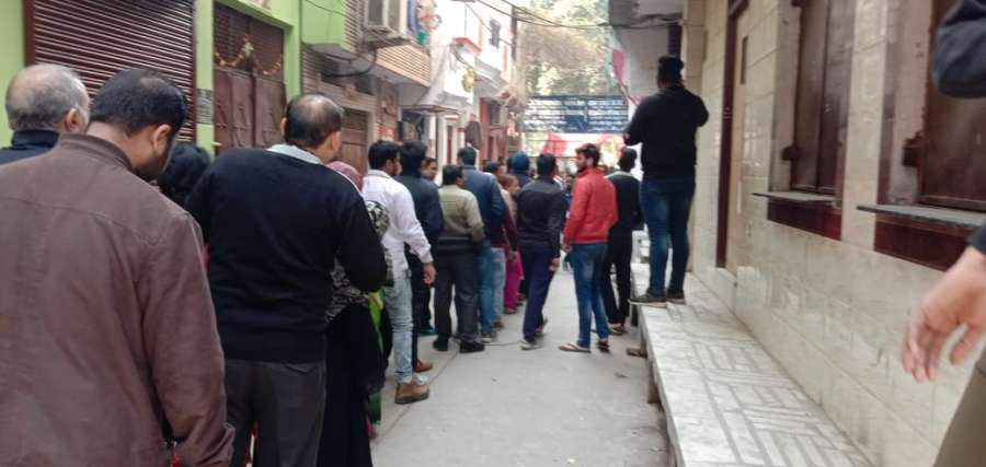 New Delhi: People queue up outside a polling station to cast their votes for the Delhi Assembly elections 2020, at Delhi's Gandhinagar on Feb 8, 2020. (Photo: IANS) by .