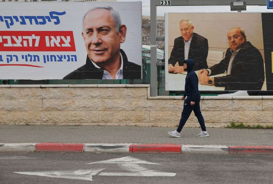 JERUSALEM, Feb. 20, 2020 (Xinhua) -- A man passes by election billboards depicting Israeli Prime Minister Benjamin Netanyahu (L) and opposition leader Benny Gantz (M) in Jerusalem on Feb. 20, 2020. Israel is heading to the third election within a year for the first time in its history after the two previous elections yielded inconclusive results, paralyzing the country's political system. (Photo by Muammar Awad/Xinhua/IANS) by .