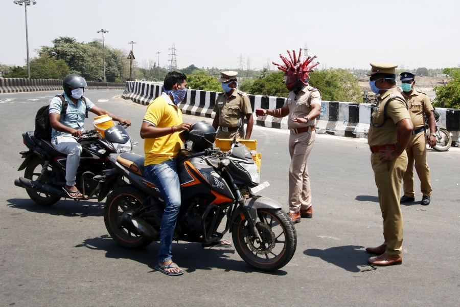 Chennai: A Chennai cop wearing a 'Corona Helmet' intercepts a lockdown violater on March 29, 2020. The cop wearing the helmet, police Inspector Rajesh Babu in collaboration with a local artist Gowtham had come with this innovative initiative to dissuade people from flouting the curfew and make them undertand the severity of the disease. The helmet that has a scary and eerie appearance, has been designed loosely based on a close up of what a singular representation of the virus looks like. Coronavirus (COVID-19) has a crown-like appearance and the spikes on its surface gives this virus its family name, corona which means crown in Latin. As per the latest statistcs from the World Health Organsation, there are 575,444 cofirmed cases of Coronavirus across 202 nations with 26,654 deaths. Cases across India surged to 974 with 109 new cases on Saturday. The death toll in the country touched 27 with Delhi, Kerela, Telangana, Gujarat and Maharashtra confirming one death each. In order to contain the spead of COVID-19, Prime Minister Narendra Modi had announced a 21 day nationwide lockdown imposed in 560 districts in 32 states and union territories across the country that came into effect on the intervening night of March 24 and 25 and shall continue till April 14. (Photo: IANS) by .