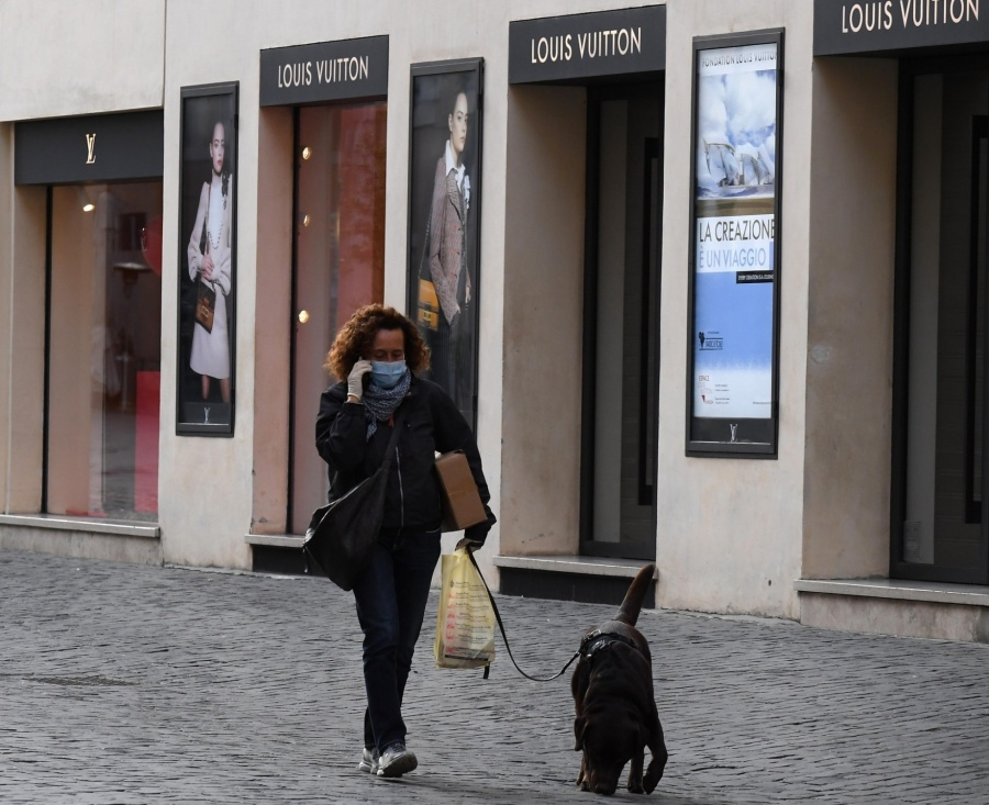 BERLIN, March 15, 2020 (Xinhua) -- A woman wearing a face mask walks a dog on the shopping street Via dei Condotti in Rome, Italy, on March 12, 2020. TO GO WITH XINHUA HEADLINES OF MARCH 15, 2020. (Photo by Elisa Lingria/Xinhua/IANS) by .