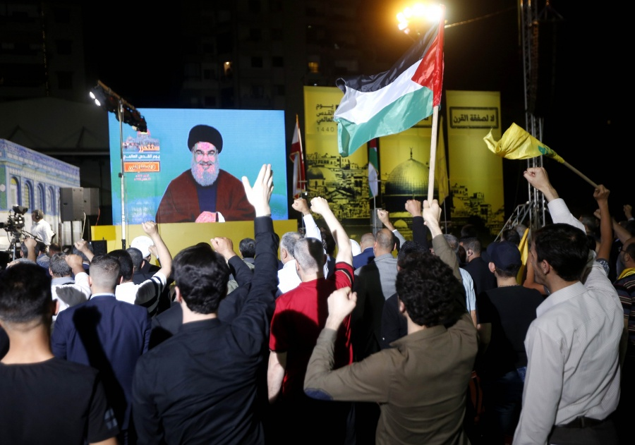 """BEIRUT, May 31, 2019 (Xinhua) -- Supporters listen to Hezbollah leader Sayyed Hassan Nasrallah's speech on a screen during a rally in the southern suburb of Beirut, Lebanon, on May 31, 2019. Hezbollah leader Sayyed Hassan Nasrallah on Friday vowed to fight fiercely against U.S. President Donald Trump's plan, known as the Deal of the Century, NBN local TV Channel reported. """"This deal is a shame and it should be confronted by everybody. We are capable of facing this conspiracy,"""" Nasrallah said in a televised speech marking al-Quds Day, an occasion to express support for the Palestinians. (Xinhua/Bilal Jawich/IANS) by ."""