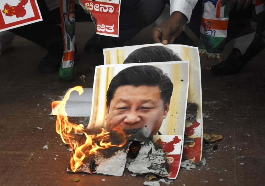 Bengaluru: Youth Congress activists burn the posters of Chinese President Xi Jinping during protest against the brutal attack on Indian Army personnel at Galwan valley at the Line of Actual Control that has killed 20 Indian soldiers during the Indo-Chinese face off in Ladakh; in Bengaluru on June 17, 2020. (Photo: IANS) by .