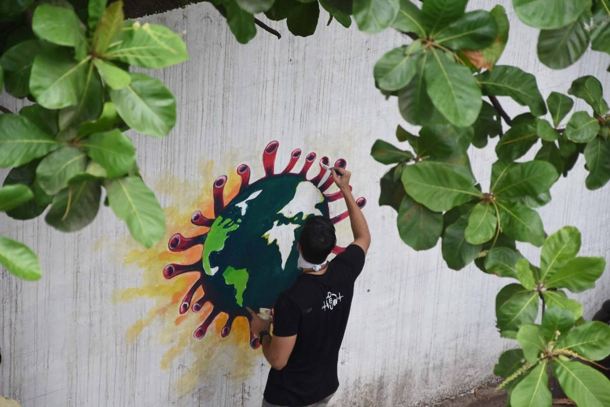 Mumbai: An artist paints a wall graffiti of the 'Earth trapped in COVID-19 pandemic' in Mumbai on June 2, 2020. (Photo: IANS) by .
